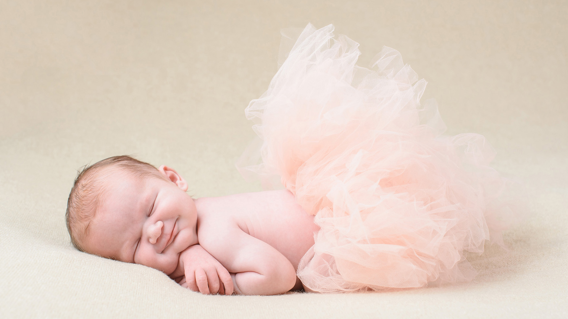 Smiling baby in a pink tutu