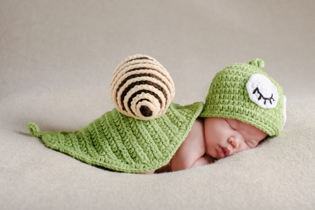 newborn baby in a snail outfit